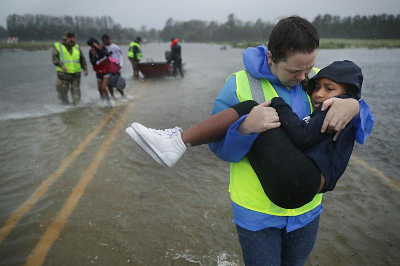 Volunteers help rescue three children from their flooded home in James City N.C. on Friday. More