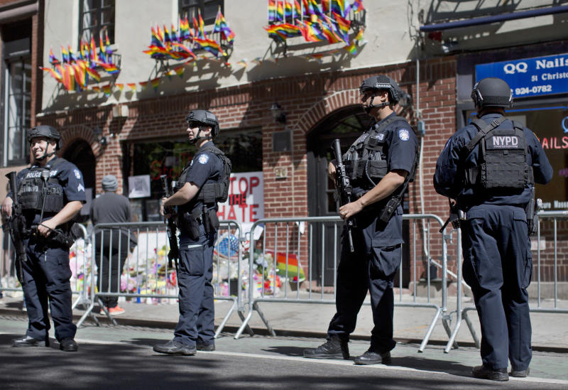 June 14, 2016 -- Armed police officers stand guard outside the historic Stonewall Inn in New York as people congregate to pay their respects for the the victims and survivors of the Orlando nightclub shooting. The officers are heavily armed and equipped, in a manner typical of the NYPD's counterterrorism unit and Emergency Service Unit - the NYPD's equivalent of SWAT officers.(AP Photo/Mary Altaffer)