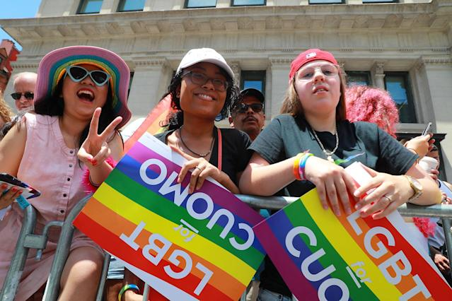 <p>A young woman flashes peace sign as parade watchers hold LGBT signs during the N.Y.C. Pride Parade in New York on June 25, 2017. (Photo: Gordon Donovan/Yahoo News) </p>