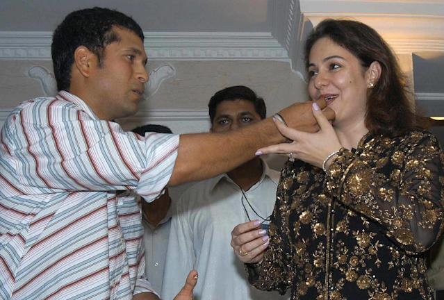 BOMBAY, INDIA: Indian cricketer Sachin Tendulkar (L) gives a piece of cake to his wife Anjali on the eve of his 31st birthday in Bombay, 23 April 2004. Tendulkar had a get-together with family and friends as he will be attending the wedding reception of his colleague Virender Sehwag who recently got married in Delhi. AFP PHOTO (Photo credit should read STR/AFP/Getty Images)