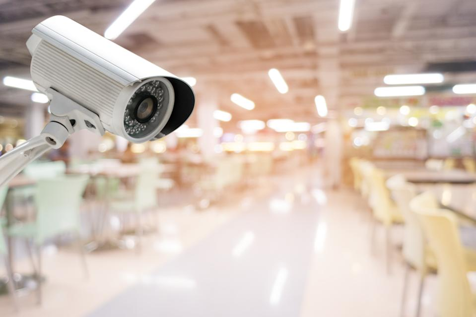 CCTV security camera with abstract blurred food court background