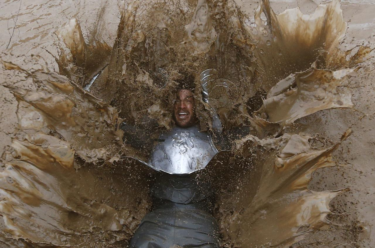 A competitor falls into muddy water during the Tough Guy event in Perton, central England, January 26, 2014. The annual event to raise cash for charity challenges thousands of international competitors in a cross country run followed by an assault course consisting of obstacles including water, fire and tunnels. REUTERS/Darren Staples (BRITAIN - Tags: SPORT ATHLETICS SOCIETY TPX IMAGES OF THE DAY)