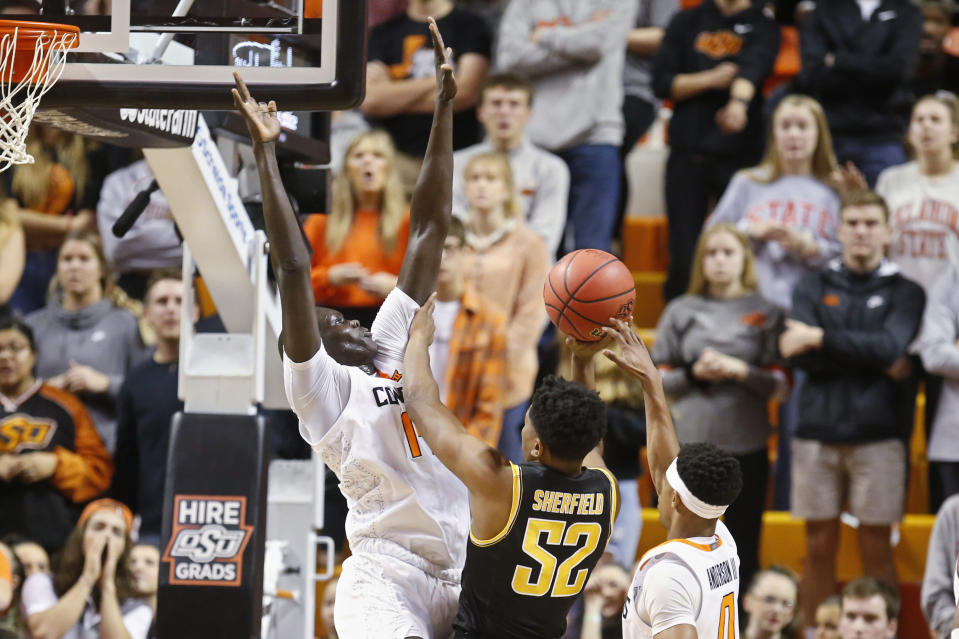 Wichita State guard Grant Sherfield (52) shoots between Oklahoma State forward Yor Anei, left, and guard Avery Anderson III, right, in the first half of an NCAA college basketball game in Stillwater, Okla., Sunday, Dec. 8, 2019. (AP Photo/Sue Ogrocki)