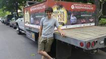 In this June 12, 2016 photo provided by Bird and the Bees Honey, beekeeper James Cook stands in front of a truck in Minneapolis. Cook, now 25, filmed a documentary while driving cross-country to raise awareness about the health of honey bees and the impact of pesticides and other stressors. He ultimately testified before Congress about this. (Bird and the Bees Honey via AP)