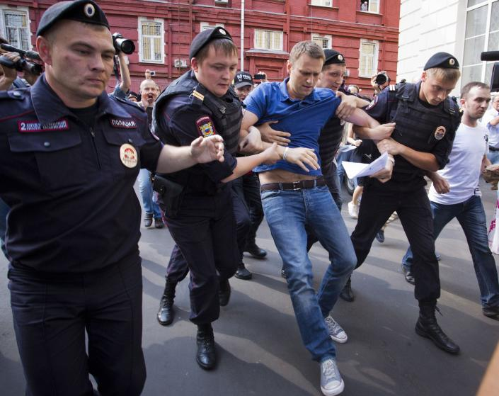 FILE - In this July 10, 2013, file photo, police officers detain Russian opposition leader Alexei Navalny, center, in Moscow, Russia. Navalny is an anti-corruption campaigner and the Kremlin's fiercest critic. He has outlasted many opposition figures and is undeterred by incessant attempts to stop his work. (AP Photo/Evgeny Feldman, File)