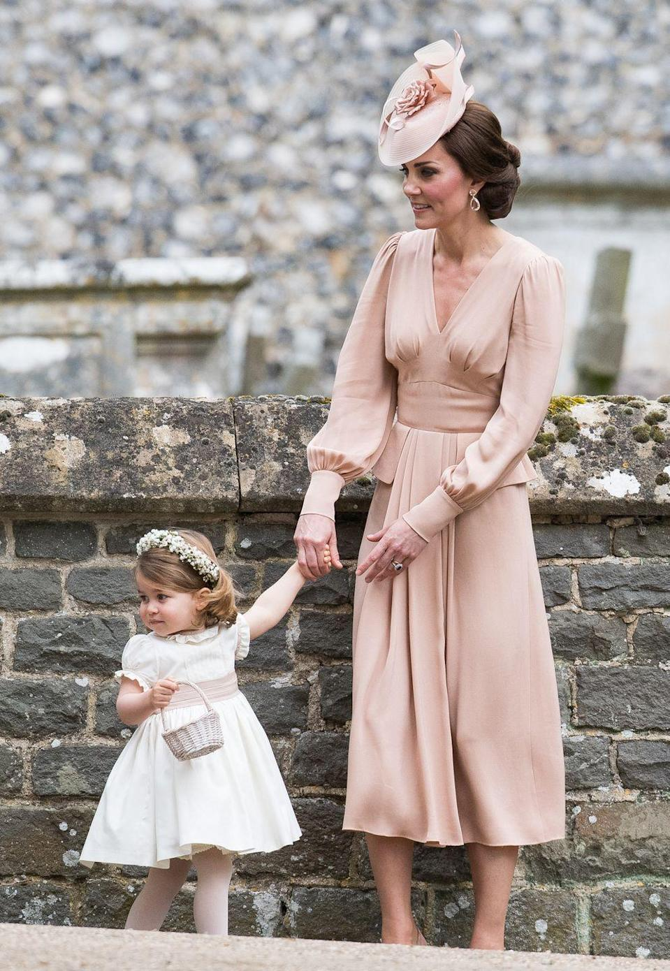 <p>The Duchess of Cambridge holds hands with daughter Princess Charlotte, then 2, who was a bridesmaid at Pippa Middleton's wedding in May 2015. This was Princess Charlotte and Prince George's first time being bridesmaid and pageboy in a wedding.</p>