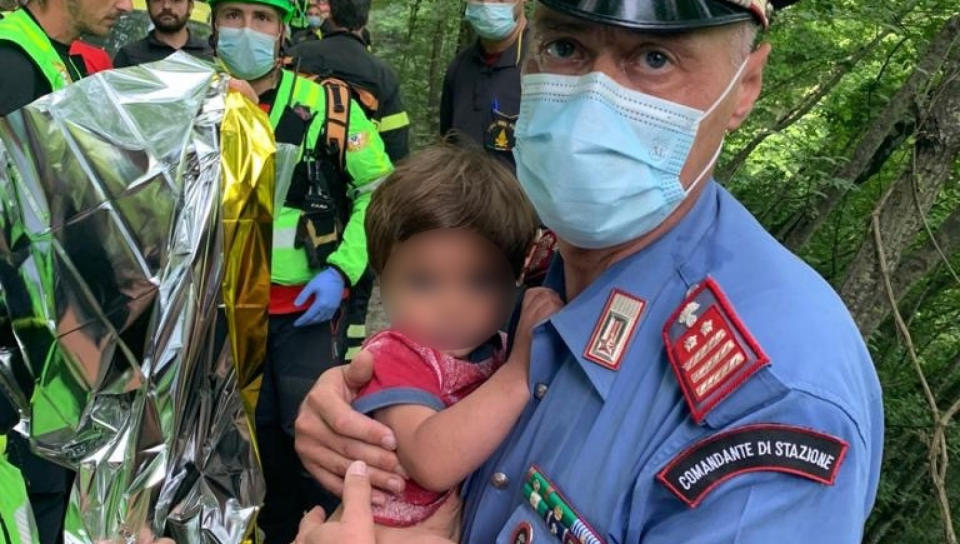 A police officer holds Nicola Tanturli, who was found after spending over 24 hours lost in the woods.
