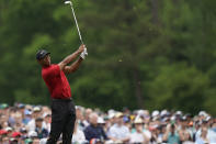 FILE - In this April 14, 2019, file photo, Tiger Woods hits on the 12th hole during the final round for the Masters golf tournament, in Augusta, Ga. Woods hit 9-iron to the fat of the green after watching two other players hit into the water. (AP Photo/David J. Phillip, File)