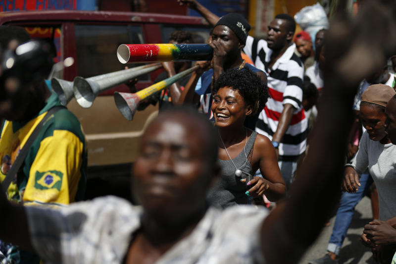 People dance as they march along with a band in Petion-Ville, Port-au-Prince, Haiti, Monday, Oct. 21, 2019. Anger over corruption, inflation and scarcity of basic goods including fuel has led to large demonstrations that began more than a month ago and have shuttered many businesses and schools. (AP Photo/Rebecca Blackwell)