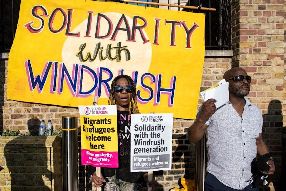 Protesters in Brixton hold signs in support of those affected by the Windrush scandalGetty