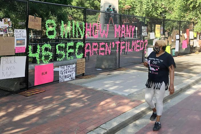A woman in Washington, D.C.'s Black Lives Matter Plaza on Tuesday looks at posters denouncing the death of George Floyd. (Joseph Peters)