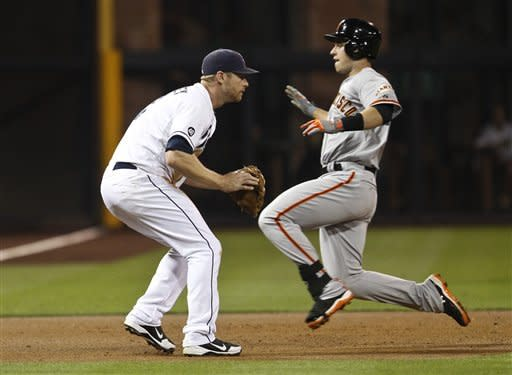 San Francisco Giants' Buster Posey goes into a slide as San Diego Padres third baseman Chase Headley awaits a late throw during a second inning triple in a baseball game Friday, Sept. 28, 2012 in San Diego. (AP Photo/Lenny Ignelzi)