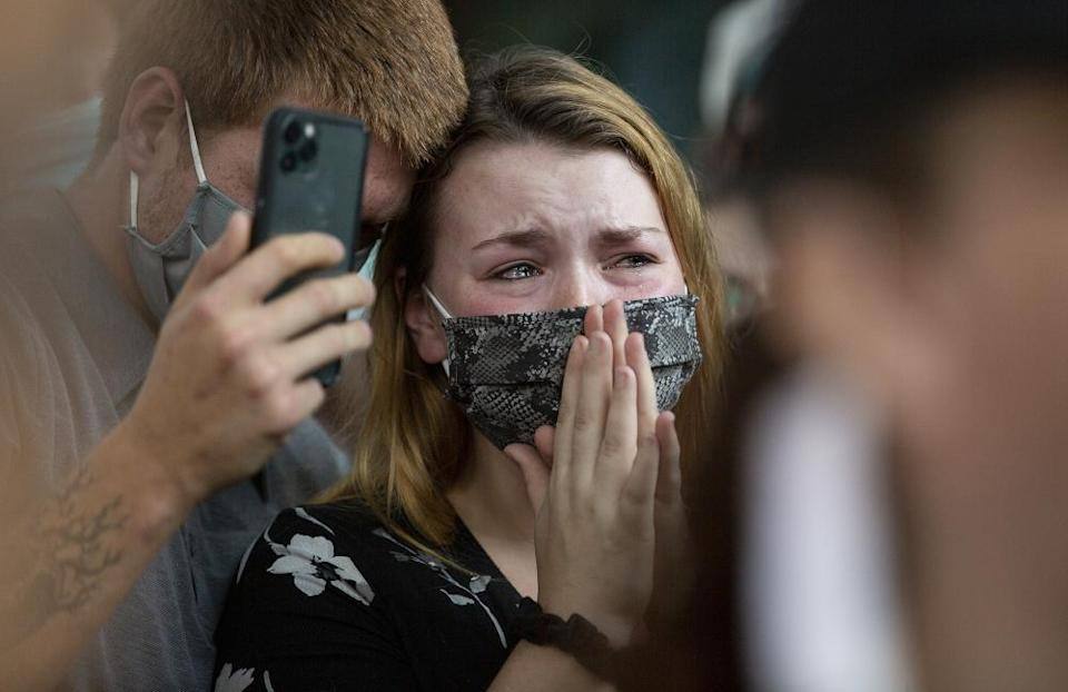 Chase Mayo comforts his wife, Anna Mayo, the sister of Garrett Foster, during a vigil in memory of Foster on 26 July 2020, in Austin, Texas.