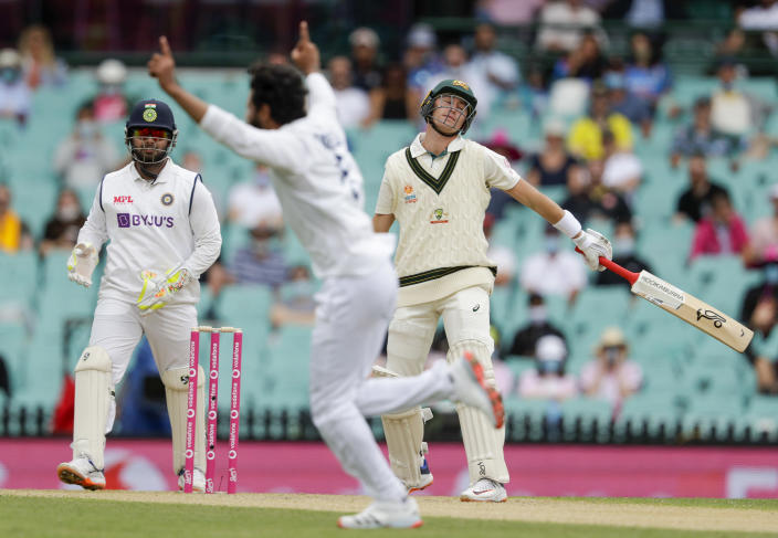 Australia's Marnus Labuschagne, right, reacts after he was dismissed off the bowling of India's Ravindra Jadeja, centre, during play on day two of the third cricket test between India and Australia at the Sydney Cricket Ground, Sydney, Australia, Friday, Jan. 8, 2021. (AP Photo/Rick Rycroft)