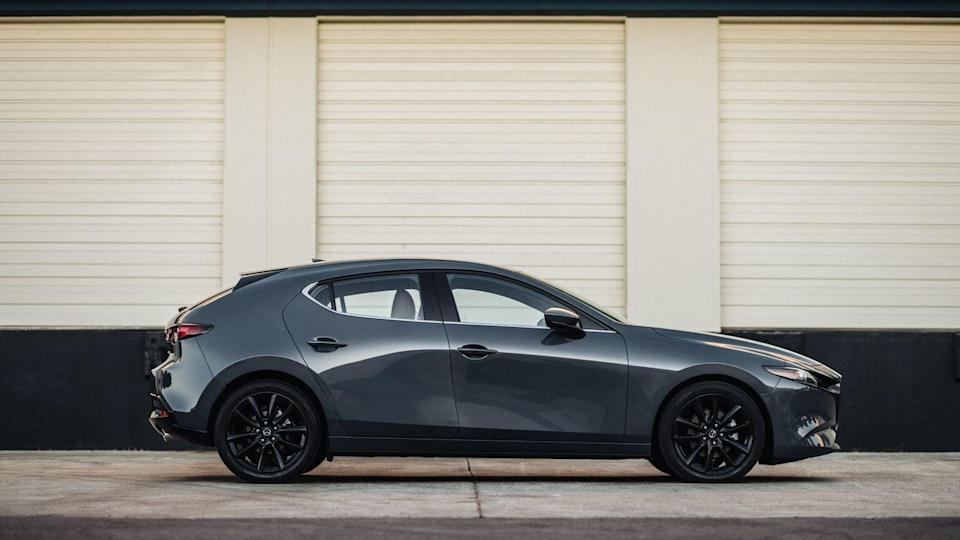 """<p>Mazda doesn't offer its smallest sedan with a stick, however, the <a href=""""https://www.caranddriver.com/mazda/mazda-3"""" rel=""""nofollow noopener"""" target=""""_blank"""" data-ylk=""""slk:Mazda 3"""" class=""""link rapid-noclick-resp"""">Mazda 3</a> hatchback is still available with one. A six-speed manual is standard in the hatch with the Premium trim level and front-wheel drive. It's paired with a 186-hp 2.5-liter four-cylinder. Cars ordered with all-wheel drive or the new 250-hp version of the turbocharged engine are automatic only.</p>"""