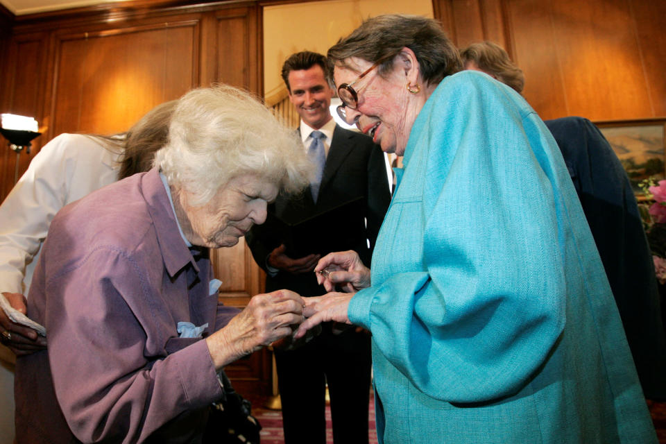 FILE - In this June 16, 2008, file photo, Del Martin, left, places a ring on her partner Phyllis Lyon, right, during their wedding ceremony officiated by then-San Francisco Mayor Gavin Newsom, center, at City Hall in San Francisco. The hilltop cottage of the couple that became the first same-sex partners to legally marry in San Francisco has become a city landmark. The San Francisco Board of Supervisors voted unanimously Tuesday, May 4, 2021, to give the 651 Duncan St. home of the lesbian activists landmark status. The home in the Noe Valley neighborhood is expected to become the first lesbian landmark in the western United States, the San Francisco Chronicle reported. (AP Photo/Marcio Jose Sanchez, File)