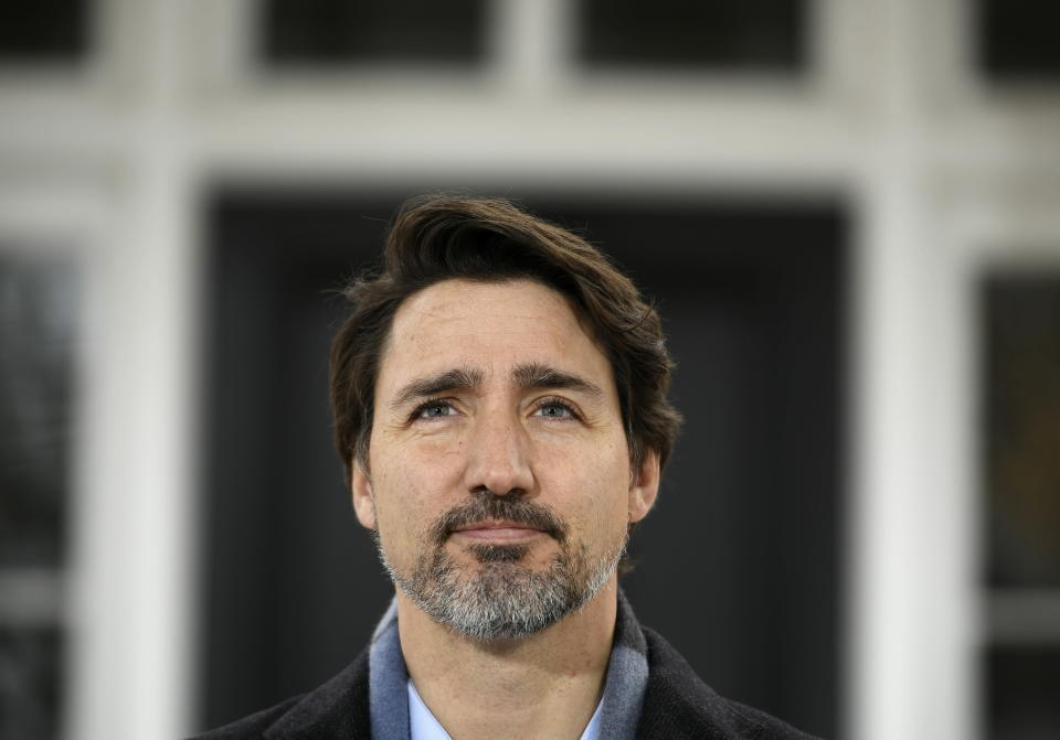 Prime Minister Justin Trudeau listens to questions during his daily press conference on COVID-19, in front of his residence at Rideau Cottage, on the grounds of Rideau Hall in Ottawa, on Saturday, March 28, 2020. (Justin Tang/The Canadian Press via AP)