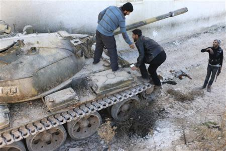 Rebel fighters stand on a tank belonging to the Islamic Front near Nairab military airport, which is controlled by forces loyal to Syria's President Bashar al-Assad, in Aleppo
