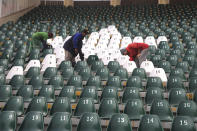Workers clean an enclosure at Gaddafi stadium as preparation for the upcoming series against Bangladesh in Lahore, Pakistan, Tuesday, Jan. 21, 2020. Pakistan will play three Twenty20 series against Bangladesh, starting from Jan. 24, at Lahore. (AP Photo/K.M. Chaudary)