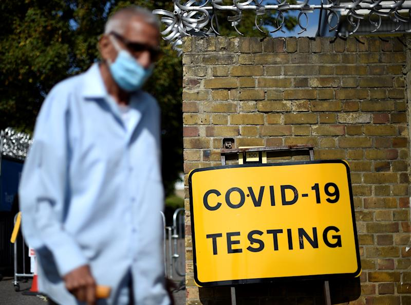 """A man wearing a face covering due to the COVID-19 pandemic, waks past a sign outside a novel coronavirus walk-in testing centre in East Ham in east London, on September 17, 2020. - British Prime Minister Boris Johnson said Thursday he could close pubs earlier to """"stop the second hump"""" of coronavirus cases, comparing the country's trajectory of resurgent transmission to a camel's profile. But the prime minister has faced stinging criticism this week over the failure to achieve the """"world-beating"""" testing and tracing system he promised by the summer. (Photo by DANIEL LEAL-OLIVAS / AFP) (Photo by DANIEL LEAL-OLIVAS/AFP via Getty Images)"""