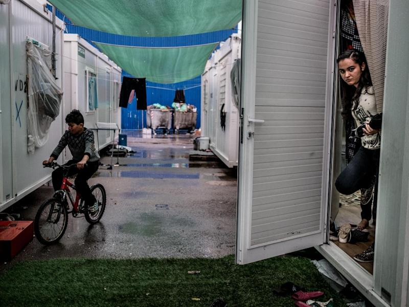 Azhar Khalil, 18, from Syria, looks out of her family's shelter at Skaramangas Refugee Camp in northern Athens, Greece