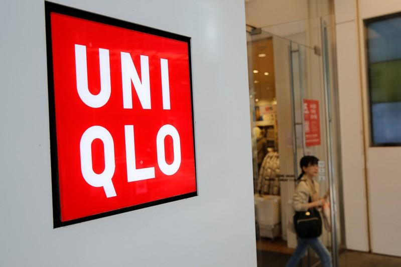 A woman walks past the logo of Uniqlo at Myeongdong shopping district in Seoul
