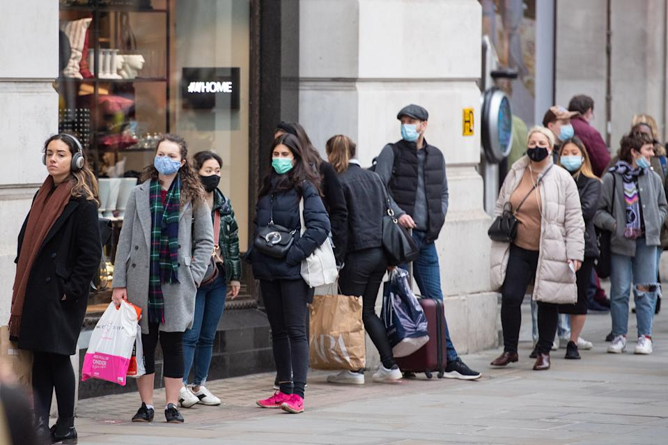Shoppers queue to enter a store on Regent Street, in central London.