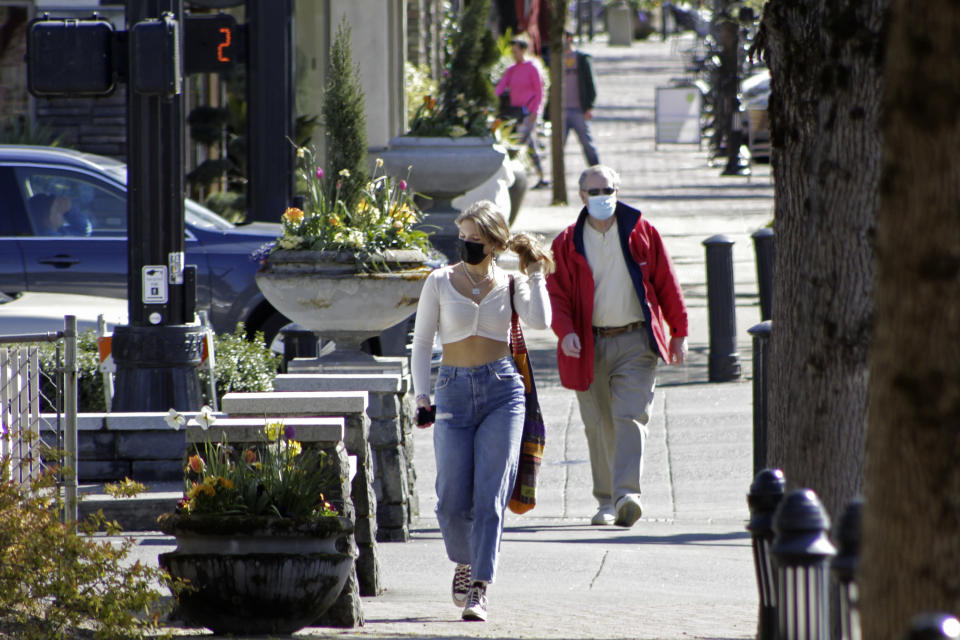 FILE - In this April 11, 2021, file photo, residents wearing masks walk in downtown Lake Oswego, Ore. Even as the federal Centers for Disease Control and Prevention moved earlier this month to ease indoor face mask-wearing guidance for fully vaccinated people, states like Oregon and Washington are still holding on to certain longtime coronavirus restrictions (AP Photo/Gillian Flaccus, File)