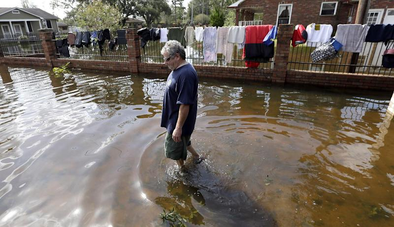 Peter Roccaforte walks through floodwaters from Hurricane Isaac at his home in Reserve, La., as some of his clothing hangs out to dry Saturday, Sept. 1, 2012. Floodwaters cover many streets and power remains out in some areas. Louisiana's Public Service Commission said more than 443,000 customers remained without electricity around Louisiana on Saturday morning, days after Hurricane Isaac crept across the state. (AP Photo/David J. Phillip)