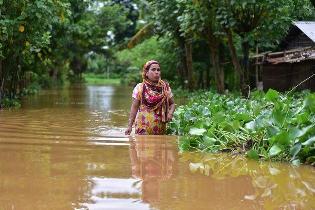 A woman wades through a flooded street in Nagaon district of Assam on 22 July 2020.