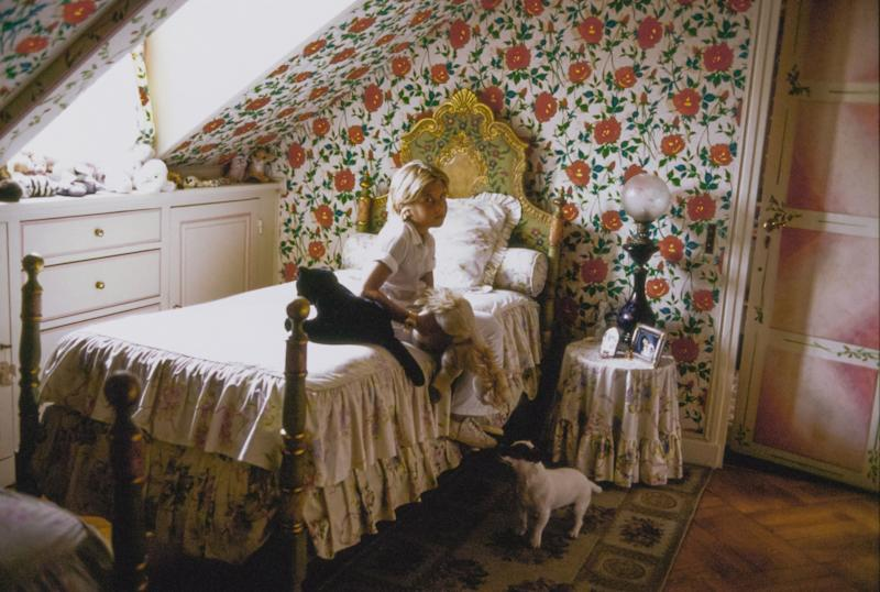 Cosima Ungaro and her Jack Russell Terrier dog, Olli, sit in her floral bedroom in the home she shares with her father, fashion designer Emanuel Ungaro and her mother, Laura Ungaro (nee Bernabei). The floral wallpaper is a rose chintz originally made for Emanuel Ungaro's couture collection by Rainbow, a collaborator. The bed linens and side table skirt are of a ruffled white floral; the white cabinets are built in under the dormer window; a lamp with a large glass globe sits on the side table. Cosima sits with two stuffed animal toys.