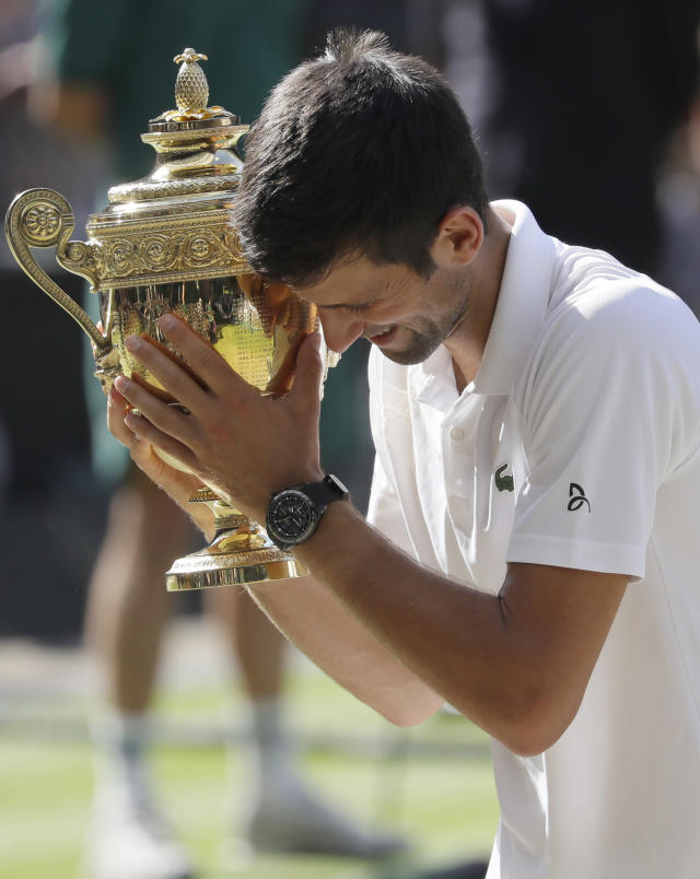 FILE - In this July 15, 2018, file photo, Serbia's Novak Djokovic holds the trophy after winning the men's singles final match against Kevin Anderson of South Africa, at the Wimbledon Tennis Championships in London. (AP Photo/Kirsty Wigglesworth, File)