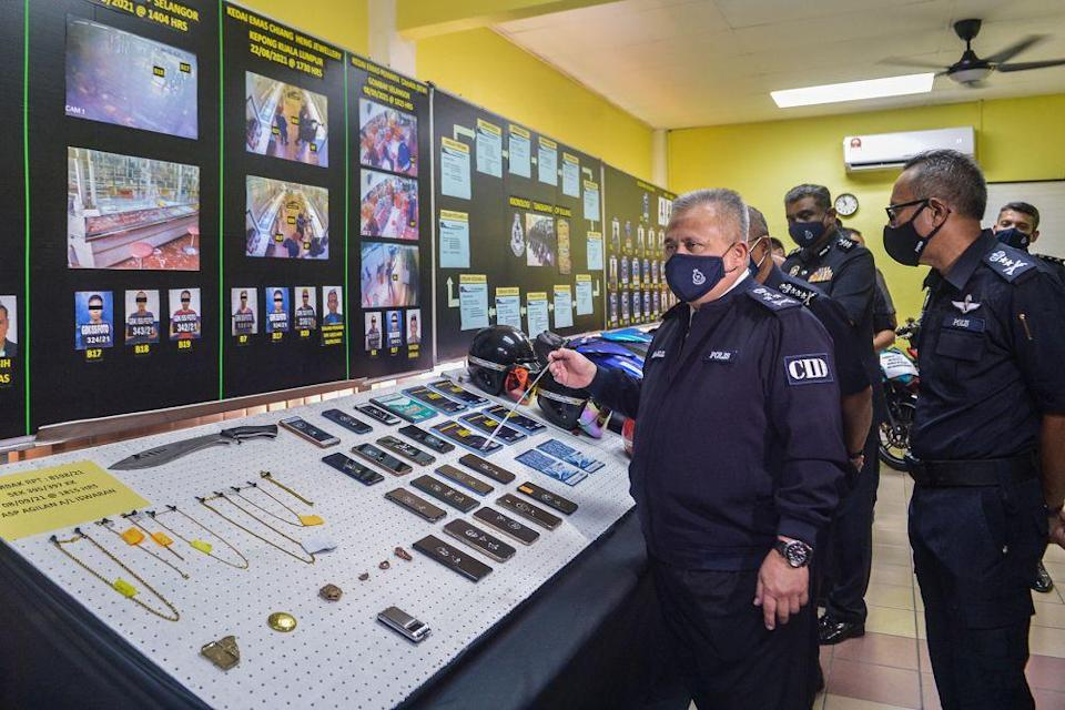 Criminal Investigation Department director Datuk Seri Abd Jalil Hassan goes through items seized from the Geng Amir @ Kecik during a press conference at the Gombak district police headquarters September 24, 2021. — Picture by Miera Zulyana