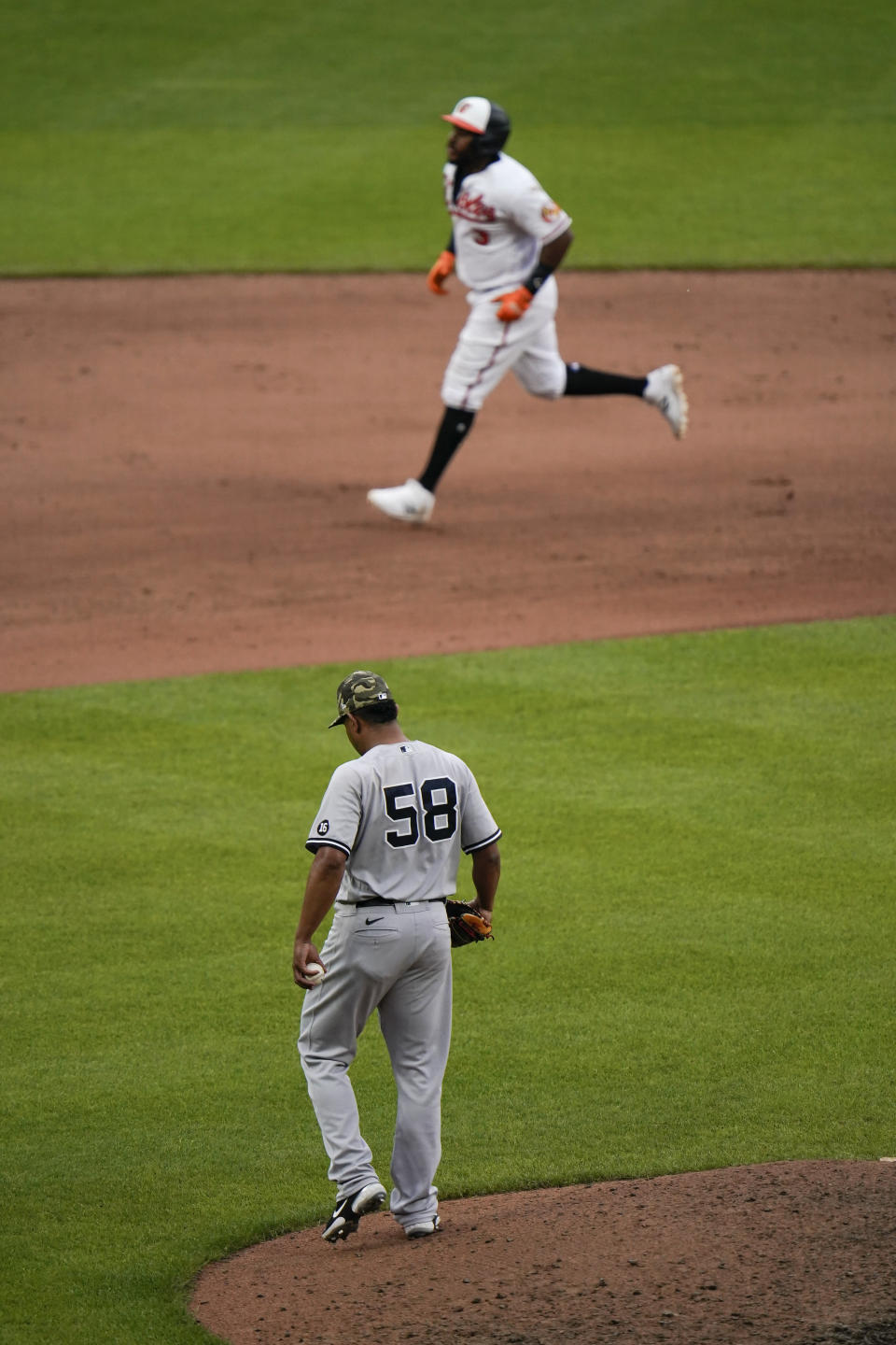 Baltimore Orioles' Maikel Franco, top, runs the bases after hitting a two-run home run off New York Yankees relief pitcher Wandy Peralta (58) during the seventh inning of a baseball game, Sunday, May 16, 2021, in Baltimore. Orioles' Pedro Severino scored on the play. (AP Photo/Julio Cortez)