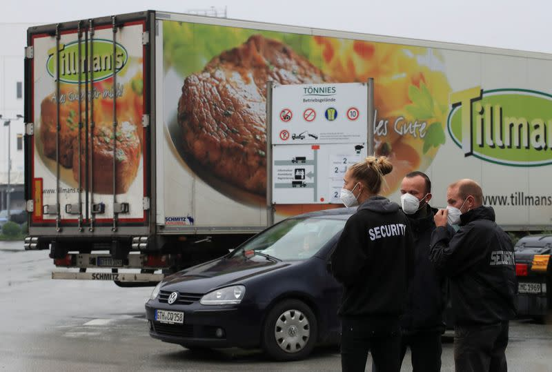 FILE PHOTO: Security personell stands in front of a meat truck as the Toennies meat factory is reopening in Rheda-Wiedenbrueck