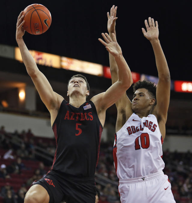 San Diego State's Yanni Wetzell shoots next to Fresno State's Orlando Robinson during the first half of an NCAA college basketball game in Fresno, Calif., Tuesday Jan. 14, 2020. (AP Photo/Gary Kazanjian)