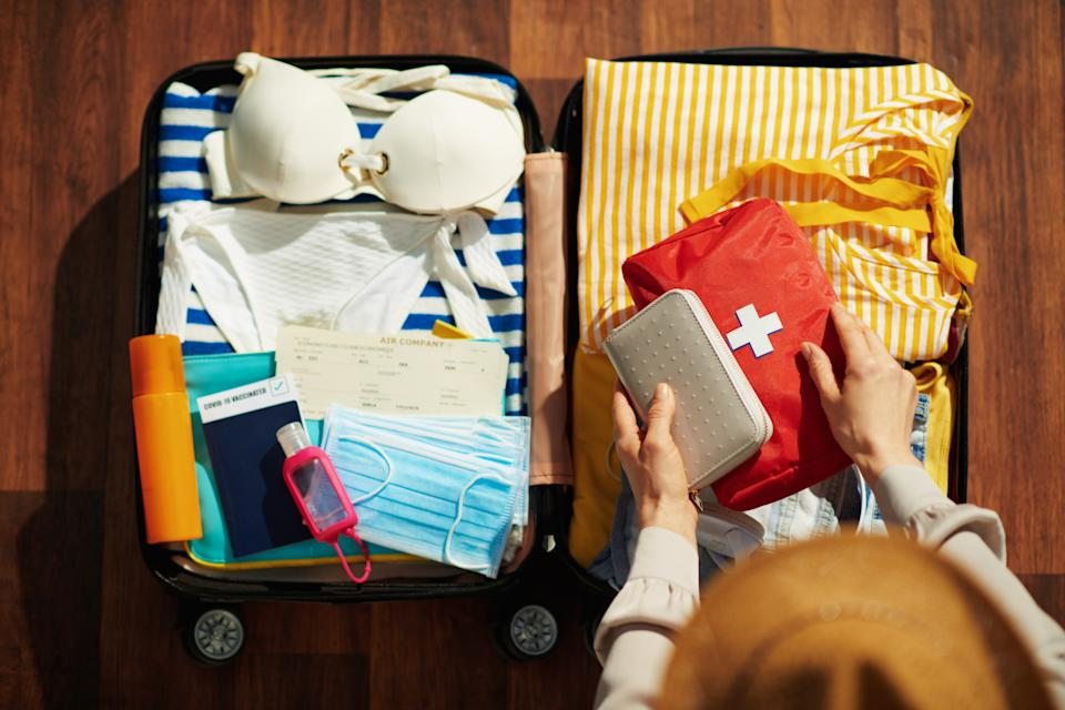 Upper view of modern female with sanitizer, trolley bag, air tickets, medical mask, straw hat, spf, first aid kit and bikini packing trolley bag in the modern house in sunny day.