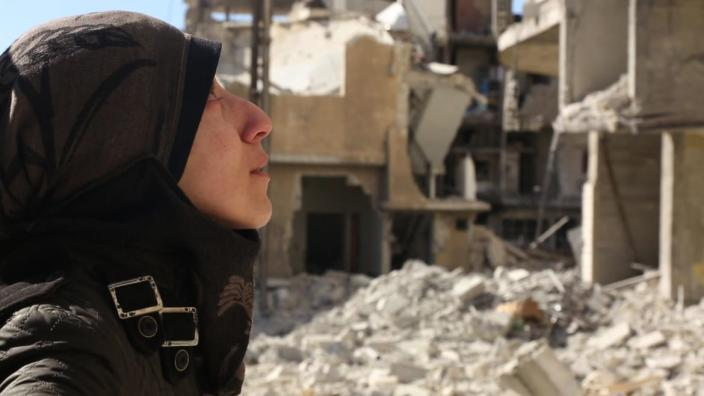 """<div class=""""inline-image__caption""""> <p>Dr. Amani Ballour amongst the rubble in Syria</p> </div> <div class=""""inline-image__credit""""> National Geographic </div>"""