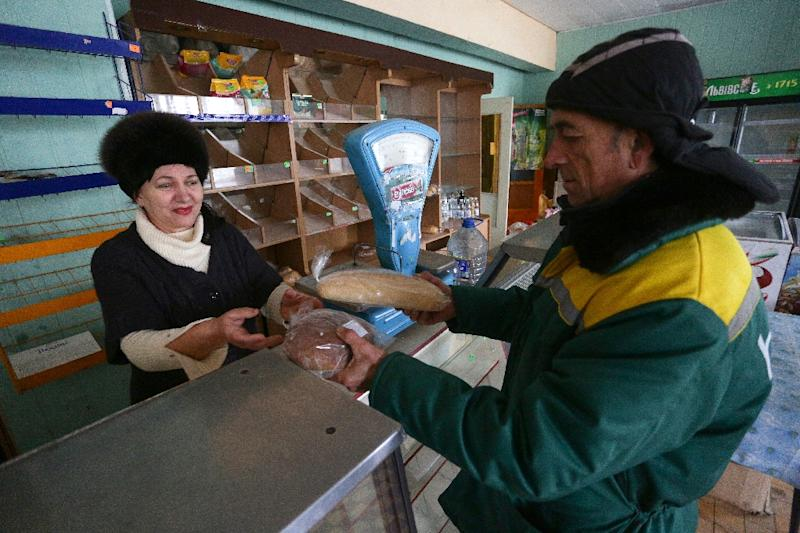 A resident receives free bread, brought by Ukrainian army, at a local store in the village of Pavlopil, in eastern Ukraine's Donetsk region (AFP Photo/Aleksey Filippov)