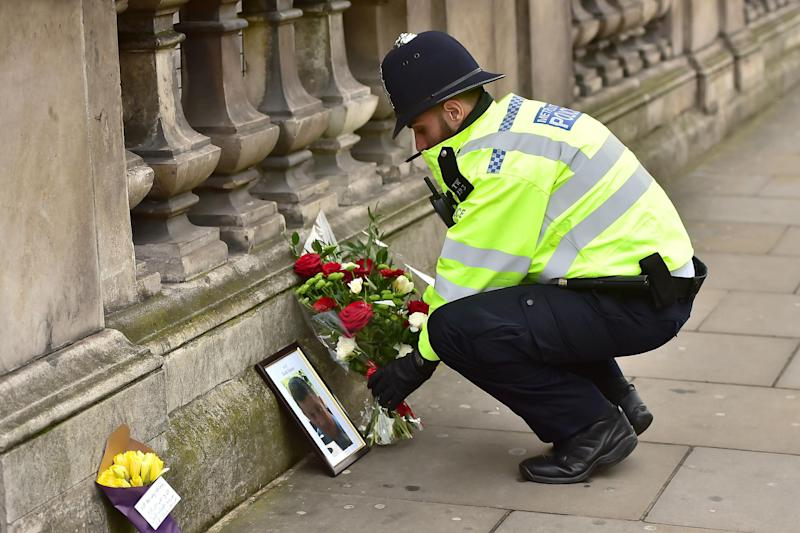 A police officer places flowers and a photo of Pc Keith Palmer on Whitehall after the Westminster attacks: Dominic Lipinski/PA