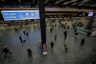 People wait to board trains with destinations including the Midlands, north of England and Scotland at Euston railway station in London, Friday, Dec. 18, 2020. The British government plans to relax restrictions on socializing and travel for five days before and after Christmas. With infections rising in the U.K., which has Europe's second-highest coronavirus death toll after Italy, there are concerns about a possible fresh surge of cases and deaths after the holidays. (AP Photo/Matt Dunham)