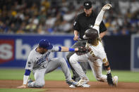San Diego Padres' Fernando Tatis Jr. (23) steals second base ahead of the tag of Los Angeles Dodgers second baseman Gavin Lux (9) during the third inning of a baseball game Wednesday, June 23, 2021, in San Diego. (AP Photo/Denis Poroy)