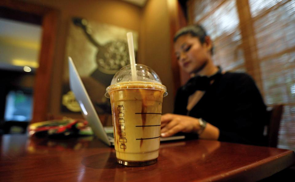 A cup of iced coffee is seen, as a woman works on her laptop, at Java Lounge coffee shop in Colombo, Sri Lanka May 4, 2017. (REUTERS/Dinuka Liyanawatte)