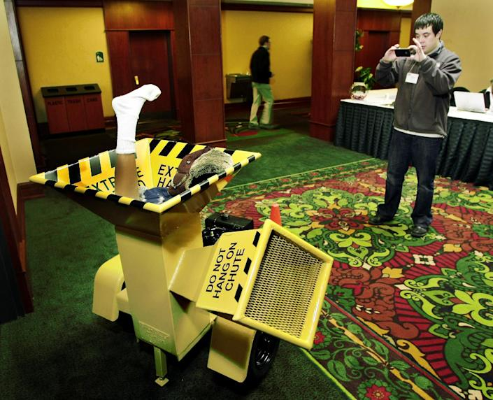 """In this photo taken April 19, 2011, Mitch Highman, of Fargo, takes a picture of a one-of-a-kind wood chipper on display during the 2011 North Dakota Travel Industry Conference at the Holiday Inn in Fargo, N.D. The chipper was made by Brian Matson and his father to resemble the one in the movie """"Fargo"""" which was also a custom-made unit. When the movie Fargo debuted in 1996, many residents in the North Dakota city were not fans of the film's dark humor, not to mention the heavy accents. But the fame and cash from the movie eventually brought many Fargo residents around. Now, 16 years later, Fargo awaits the debut of a new cable television show by the same name. And many residents are less apprehensive about how their hometown will be portrayed this time around. (AP Photo/The Forum, Dave Wallis)"""