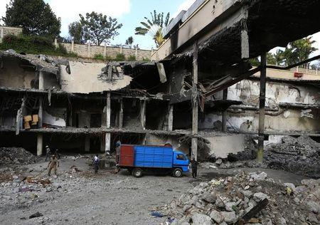 Men work on a damaged section of the Westgate Shopping Mall after al Qaeda-linked militants launched an attack on the mall in September last year, in Nairobi