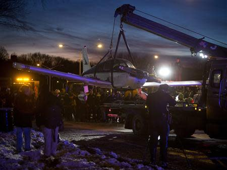 A single engine plane is lifted onto a flat bed truck after landing on Major Deegan Expressway in the Bronx borough of New York January 4, 2014. REUTERS/Carlo Allegri