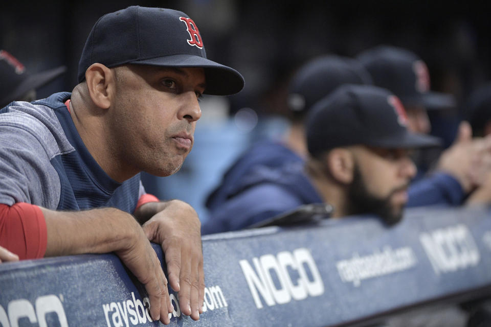 Boston Red Sox manager Alex Cora, left, watches from the dugout during the bottom of the 11th inning of a baseball game against the Tampa Bay Rays, Friday, Sept. 20, 2019, in St. Petersburg, Fla. (AP Photo/Phelan M. Ebenhack)