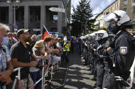 A police chain stands opposite the participants in a demonstration against the Corona measures at barrier bars in Berlin, Germany, Saturday, Aug. 29, 2020. (Bernd Von Jutrczenka/dpa via AP)