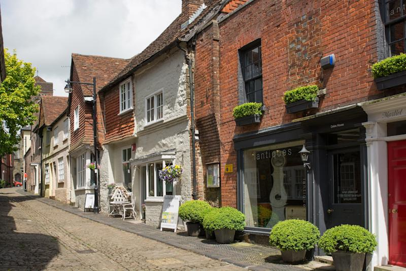 Narrow, cobbled Lombard Street in Petworth, West Sussex, England. With small shops and no people.