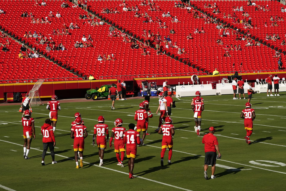 Arrowhead Stadium training camp showing players on the field and fans spread out in the stands.